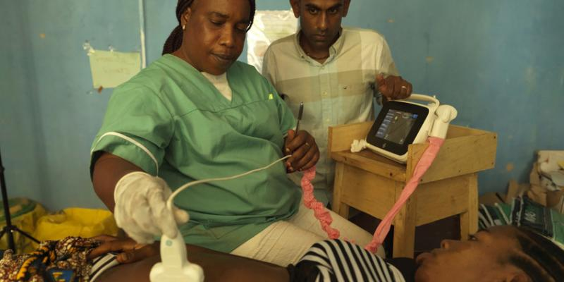 Midwife Catherine Swaray scans 17-year-old Mariama Jalloh, assisted by VSO volunteer Dr Kiran Cheedella
